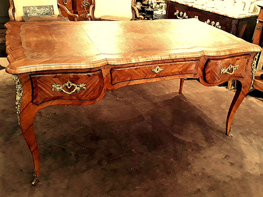 A louis xv ormolu mounted tulipwood and marquetry bureau plat by